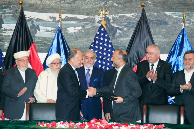 U.S. Ambassador James B. Cunningham signs the (BSA) with Afghan National Security Adviser Hanif Atmar