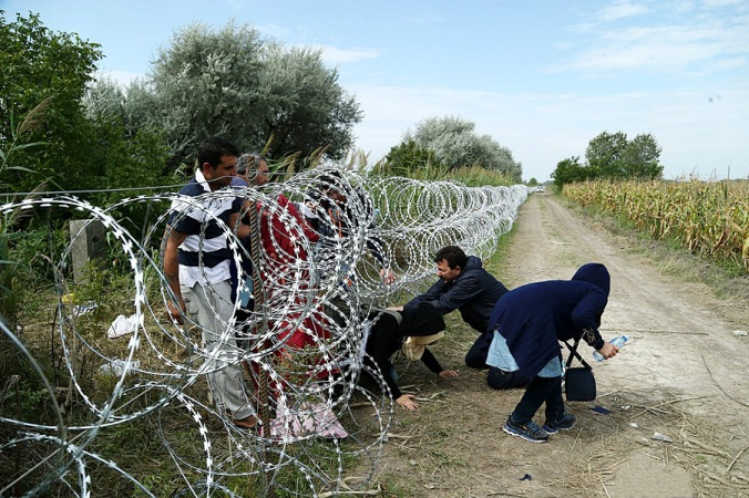 Migrants of unspecified ethnicity cross underneath unfinished border fence from Serbia into Hungary, August 2015.
