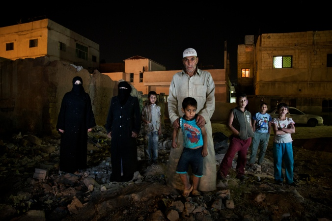 "Fawaz Rarhail Turkey, 59, from Homs, Syria, pictured with his family outside a derelict house in Al Mafraq, Jordan, which they moved into after leaving Syria. ""The army forced entry into our homes and we became afraid for our children so we were forced to"